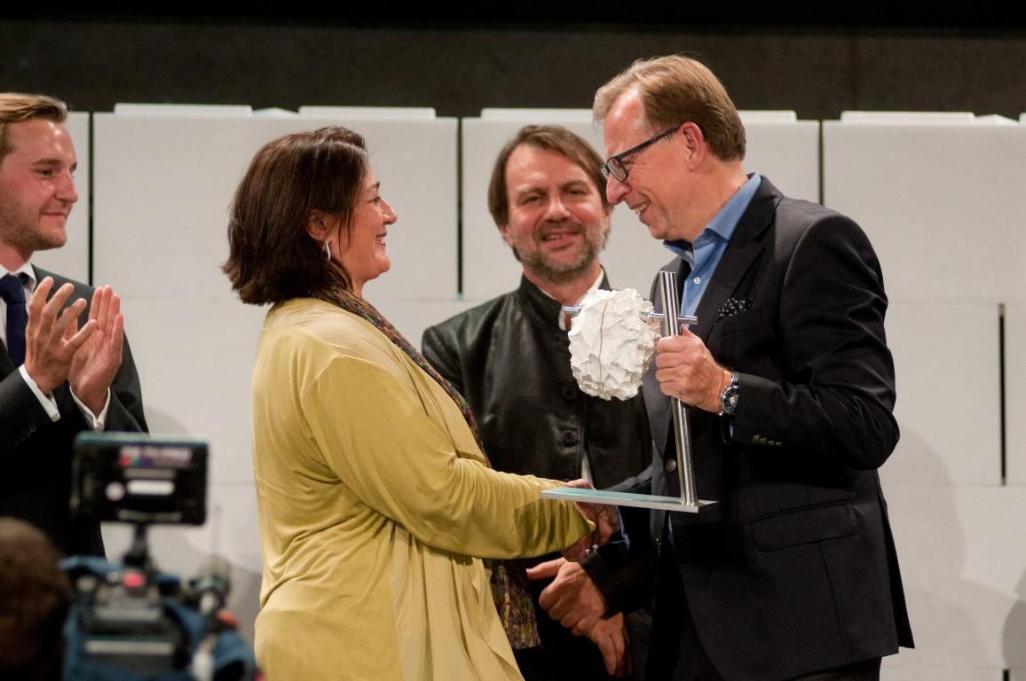 Veronica Kaup-Hasler - Intendantin des steirischen herbst - nimmt die Trophäe von Kulturlandesrat Christian Buchmann entgegen.